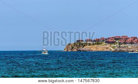SOZOPOL, BULGARIA - JULY 17, 2016: Pleasure boat cruises near Sozopol, one of the oldest Bulgarian towns founded in the 7th century BC, nowadays one of the major seaside resorts in the country.