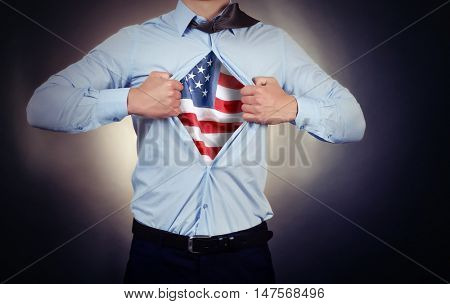 Businessman showing USA flag under suit on dark background.