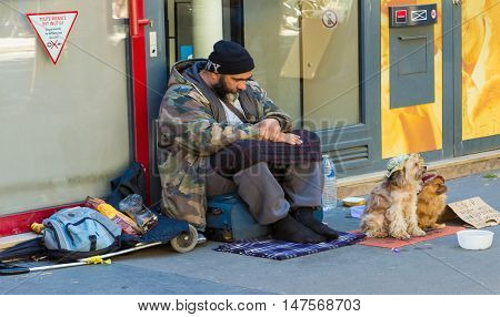 Paris France-July 09 2016: The unidentified homeless is begging with dogs on Saint Michel boulevard in Paris France.