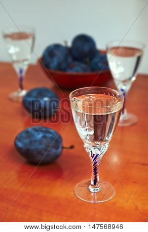 Glasses of homemade plum brandy with plums on wooden table on a white background