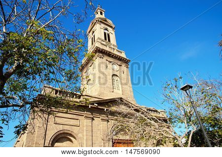 Low angle view of the Cathedral of La Serena with green trees and a blue sunny sky in Chile, South America