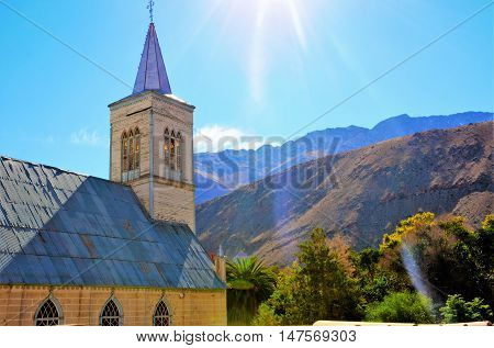 The church in Pisco Elqui from the side with a very sunny blue sky and mountain range in the background in Chile, South America