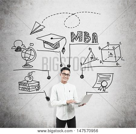 Asian man with laptop standing near concrete wall with MBA sketch. Concept of business education