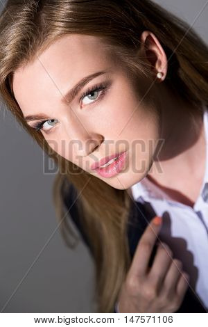 Pretty business lady looking to camera seductively. She is wearing business suit and orange nail polish. Concept of gorgeous real estate agent