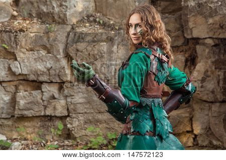 Elf Woman In Green Leather Armor Pointing On Something.