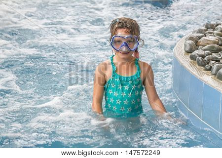 portrait of young happy caucasian child girl swimming in pool