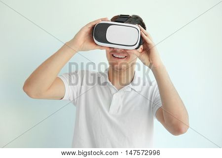 Young man wearing virtual reality glasses on white background