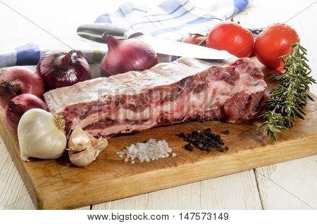 raw pork ribs with fresh tomato purple onion garlic rosemary coarse salt and peppercorn on a wooden board