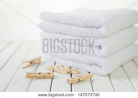 Stack of three white fluffy cotton bath towels and wooden clothespins on the background of white boards