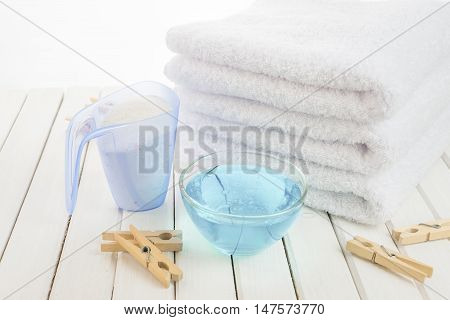 Stack of three white fluffy bath towels washing powder in measuring cup blue fabric softener in a transparent glass bowl and wooden clothespins on the background of white boards