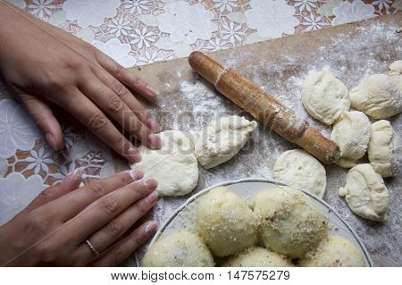 The process of preparation of Ukrainian dumplings. Plate with dumplings and ready for new billet located on the work surface. Dough flour and tools lying on a cutting board.