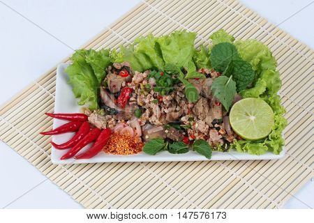 Spicy and sour mixed herb salad with pork and chicken on bamboo and white. Side view.