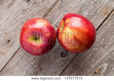 Red apples on wooden background top view.
