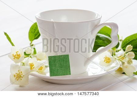Herbal tea and blooming wild flowers on a white wooden background
