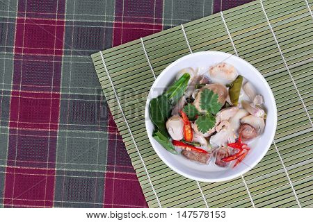 Chicken and galangal in coconut milk soup and herb on bamboo red green.  Top view