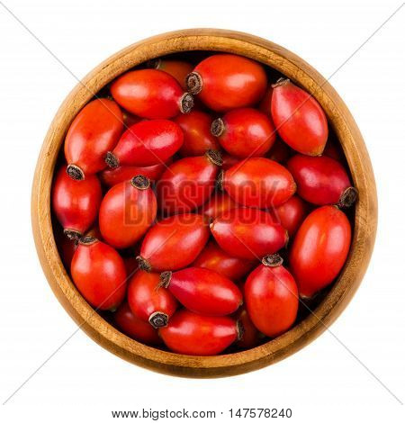 Rose hips in wooden bowl over white, also rose haw or rose hep. Ripe red fruits of roses. Used for herbal teas, jam and can be eaten raw. One of the richest vitamin C sources available in plants.