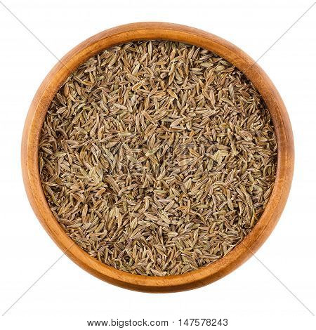 Cumin seeds in a wooden bowl on white background. Dried whole fruits of Cuminum cyminum, used as a spice in cuisine for its distinctive flavour and aroma. Isolated macro photo close up from above.