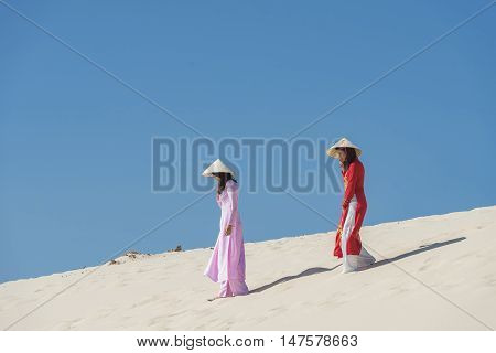Vietnamese Ao dai dress walking on the white sand beach.