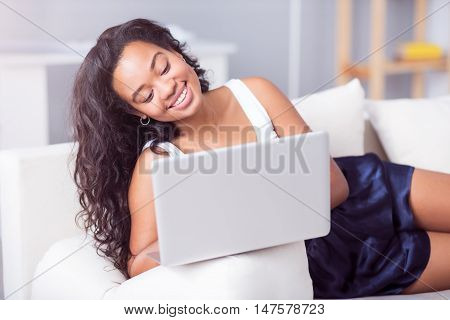 Time to rest. Cheerful happy young woman sitting on the couch and resting while suing laptop