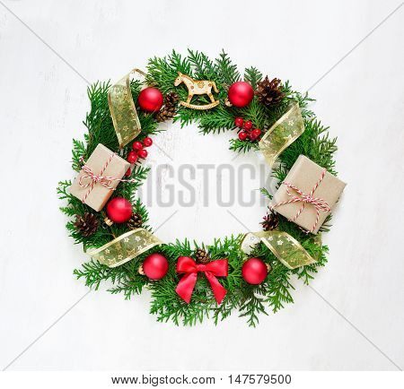 Christmas wreath made of fir twigs decorated with Xmas decorations on a wooden background