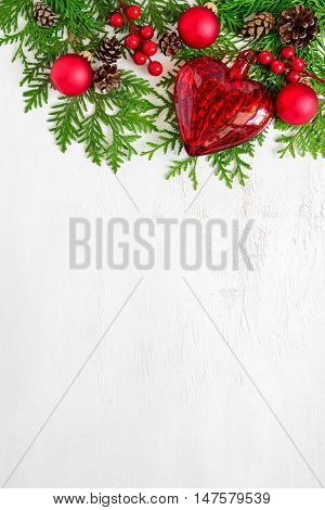 Xmas or New Year background holiday plain composition made of Christmas decorations and fir twigs on a wooden background flat lay view from above vertical orientation