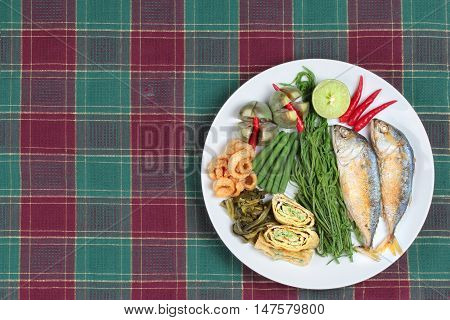 Ready side dish of deep fired mackarel,vegetable omelet,crispy pork rind,pickle lettuce,halve green lemon,red chili and boiled of eggplant,lentils,acacia  on wood. Have text space on left.