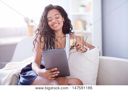 Full of gladness. Cheerful beautiful young woman sitting on the couch and holding gold card while using tablet