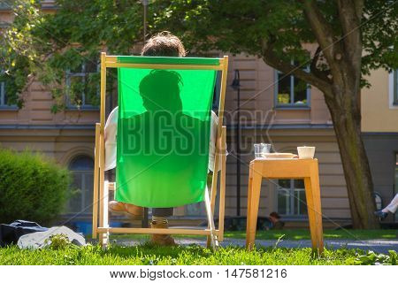 Silhouette of relaxed man chilling on deckchair in urban city park