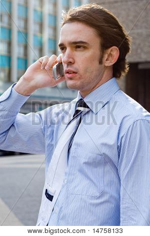 Young well dressed business man talks on cell phone