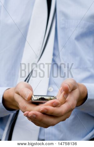 Young well dressed business man holding a cellphone