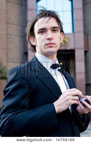 young handsome businessman (corporate executive) is using his palmtop (PDA)