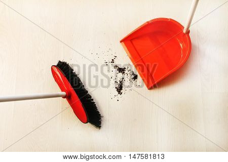 Cleaning house dust with a broom and dustpan