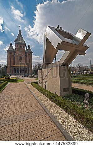 TIMISOARA ROMANIA - MARCH 18 2016: Fisheye view with the Metropolitan Cathedral and the memorial monument of the deads in anti-communist revolution from december 1989 in Timisoara Romania.