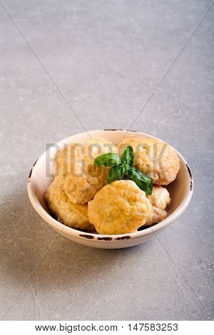 Chicken meatballs in a bowl over grey surface