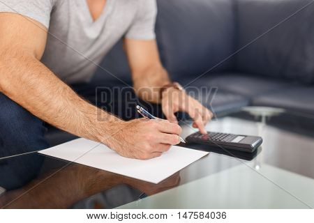 Man hands doing calculation on blank paper closeup