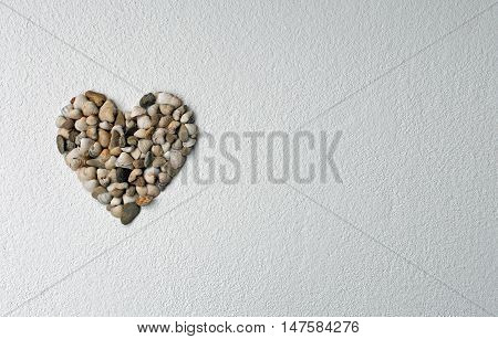 Heart of shells on textured plaster, copy space