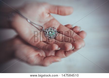 Jeweller keeps in hands beautiful handmade jewellery