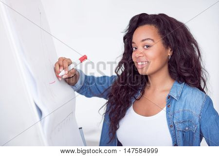 Express your idea. Positive beautiful delighted woman drawing on the board and smiling while working on the project