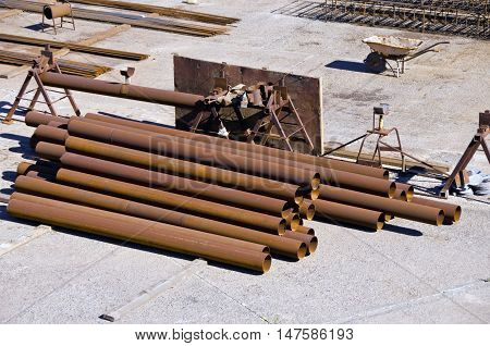Stack of metal pipes in construction area on sunny day