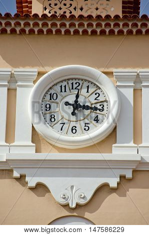 Street clock on pink old house facade