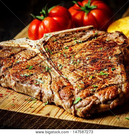 Grilled T-bone steak seasoned with spices and fresh herbs served on a wooden board with fresh tomato , roast potatoes and red hot chili peppers