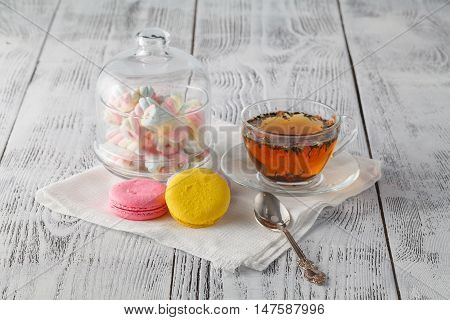 Colorful Macaroons With Cup Of Tea On Color Wooden Table