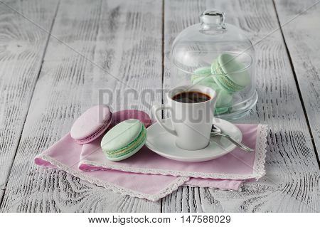 Green macaroons with coffee cup on whit table