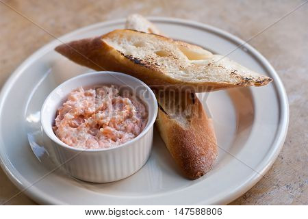 Pink salmon rillette. Pate of smoked fish in white plate, toasted baguette bread. soft focus, closeup.