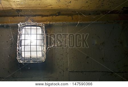 Shining old light covered in metal grill and cobwebs in against dirty, peeling painted wall.