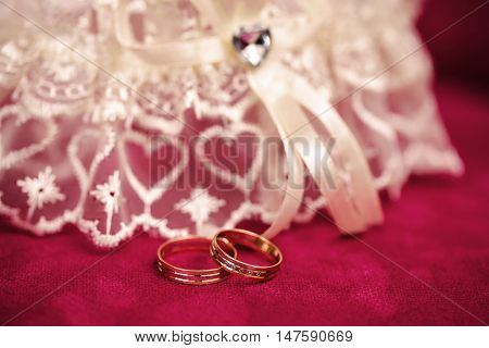 Garter of the bride and two golden rings wedding composition