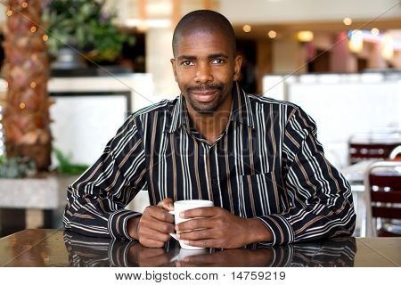 african man drinking coffee in a cafe