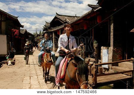 Shu He China - April 26 2006: Visitors riding miniature horses along old stone streets of the ancient Naxi village