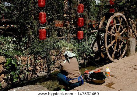 Shu He China - April 26 2006: Woman washing clothing in a fresh-water village stream near an old wooden water wheel