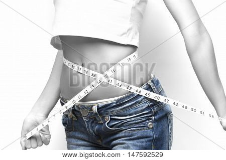 Close-up of a slim figured woman measuring her waist black and white toned